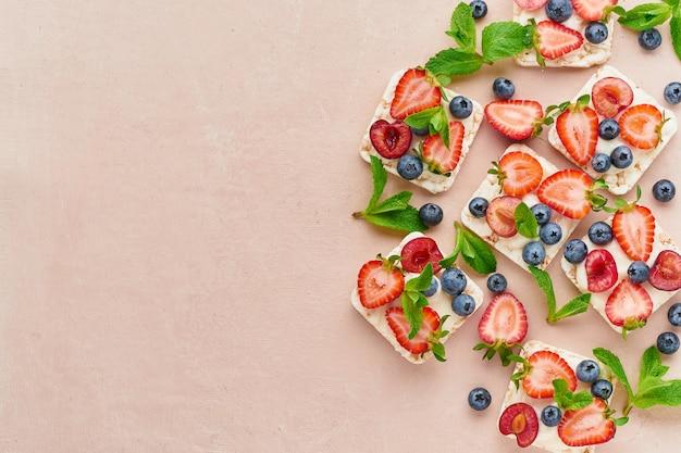 Crispbread de la subida con concepto colorido de las bayas y de las frutas en la opinión superior del espacio de la copia del fondo de la terracota
