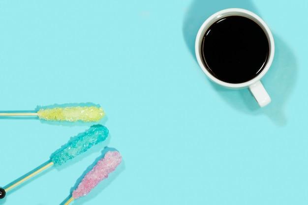 Cristal de azucar en palo de madera con cafe caliente.