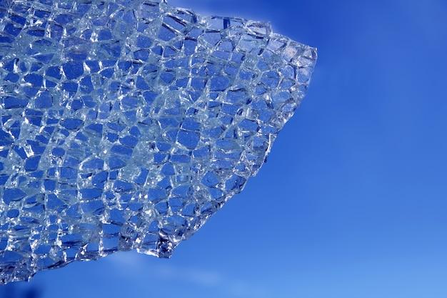 Cristal roto agrietado sobre fondo azul