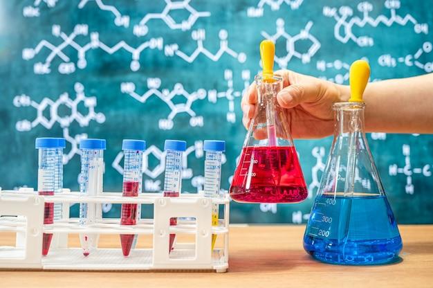 Cristalería de laboratorio con fondo de pizarra con diversas fórmulas químicas