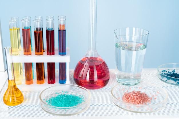 Cristalería de laboratorio químico con varios líquidos de colores en la mesa