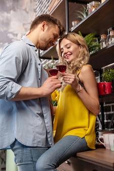 Cristales ruidosos. linda pareja amorosa de recién casados golpeando sus vasos con vino tinto, pasar tiempo en casa