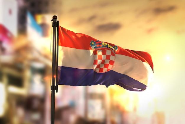 Croacia bandera contra la ciudad borrosa de fondo a la salida del sol retroiluminación