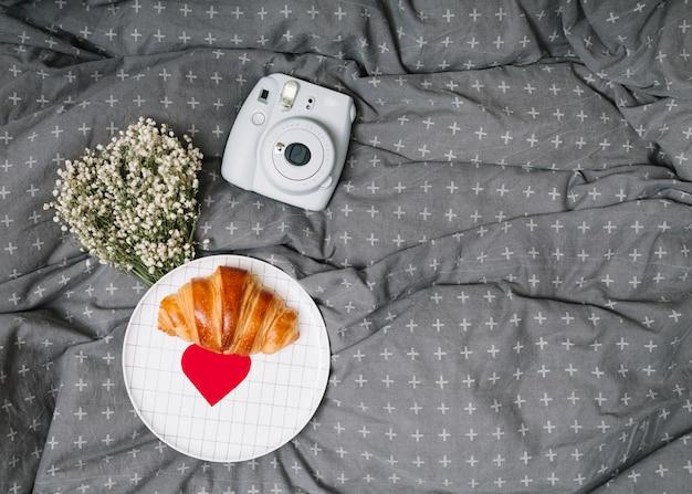Croissant y adorno corazón de papel en un plato cerca de las plantas y la cámara