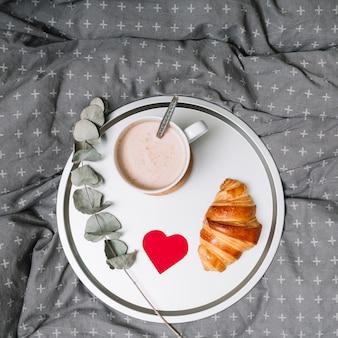 Croissant, adorno de corazón, ramita y copa de bebida en bandeja.