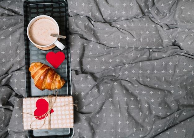Croissant, adorno de corazón, taza de bebida y caja de regalo en bandeja
