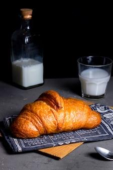 Croissant de aire y vaso con leche