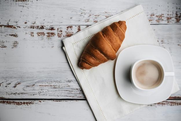 Croissant y una blanca taza de café en una mesa de madera sobre una servilleta