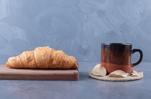 Croissant con café. croissant francés sobre tabla de madera y taza de espresso.