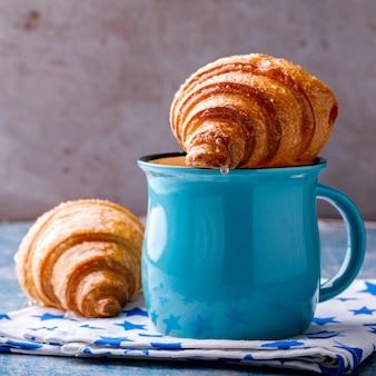 Croissant y café con leche. desayuno recién horneado.