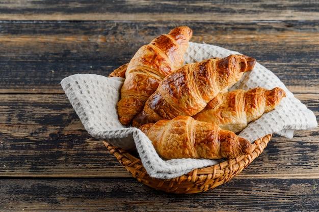 Croissant en una cesta en la mesa de madera, vista de ángulo alto.