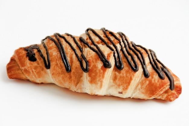 Croissant de chocolate sobre fondo blanco se vierte chocolate en la parte superior