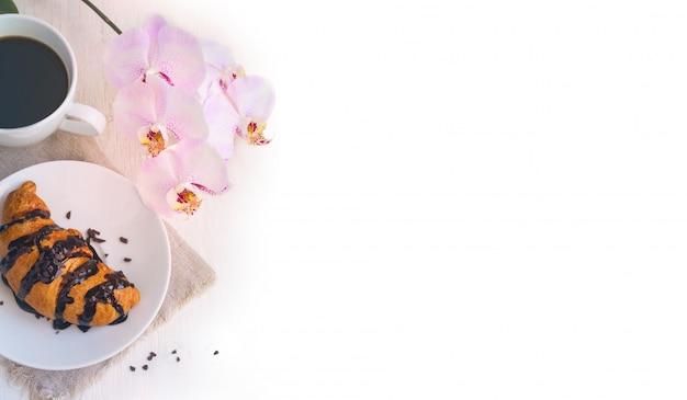Croissant con chocolate, taza de café y una orquídea rosa sobre fondo blanco.