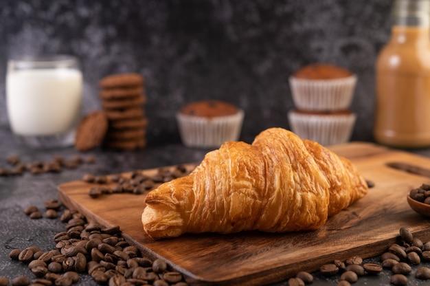 Croissant colocado sobre una plataforma de madera con granos de café sobre un piso de cemento negro.