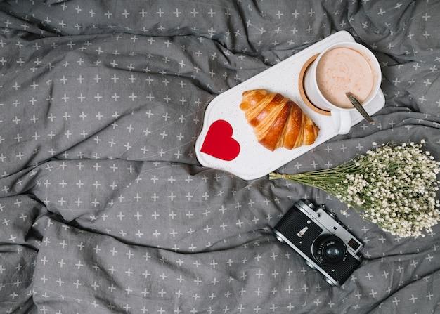 Croissant, corazón de adorno y taza de bebida en una tabla de cortar cerca de las plantas y la cámara
