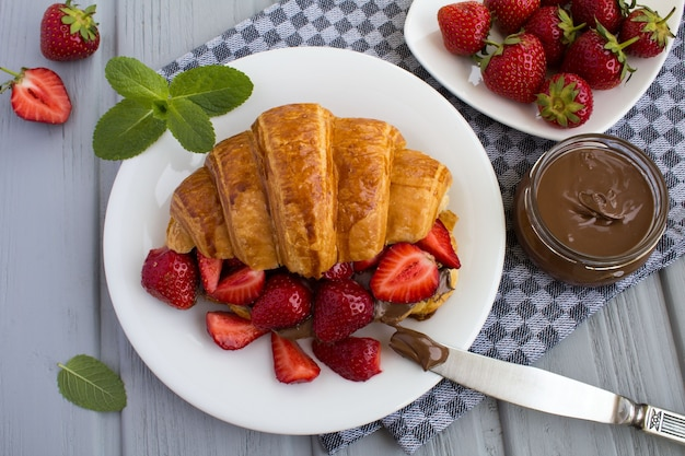 Croissant con crema de chocolate y fresa en el plato blanco en la servilleta gris.vista superior.