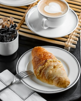 Croissant francés medio sumergido en crema de vainilla