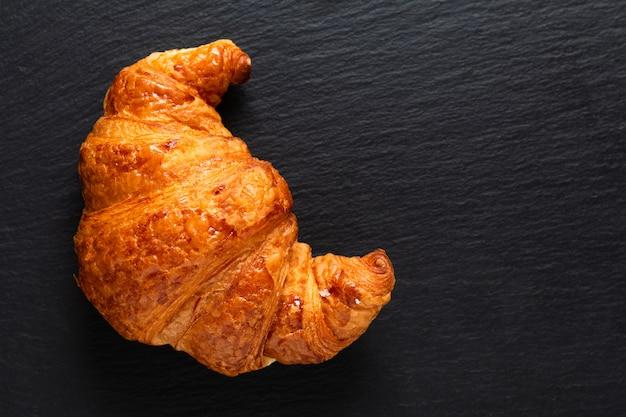 Croissant francés en pizarra negra con espacio de copia