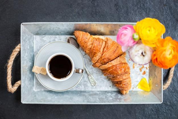 Croissant fresco, taza de café y flores de ranúnculo para el desayuno