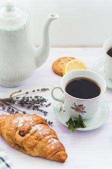 Croissant fresco con taza de té para el desayuno