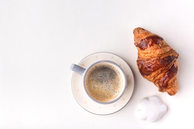 Croissant, galletas glaseadas y una taza de café sobre una mesa de madera blanca. mañana bodegón.