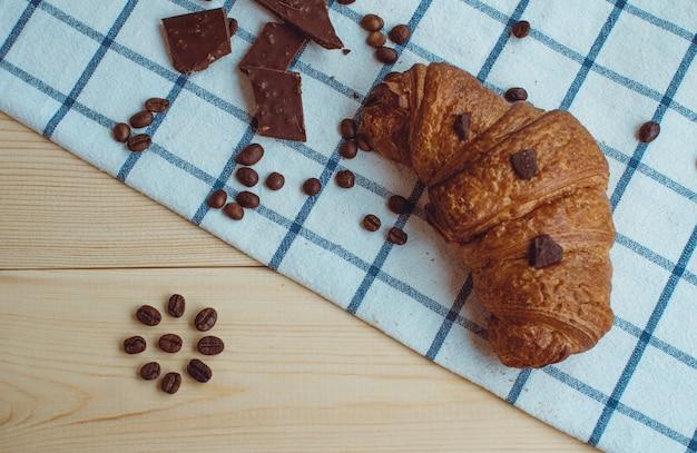 Croissant, granos de café y chocolate en una servilleta de cocina y sobre un fondo de madera. la vista desde arriba.