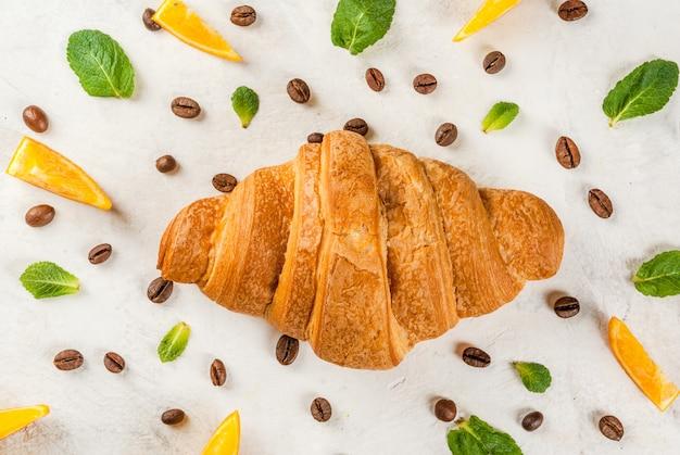 Croissant con granos de café, naranjas y hojas de menta.