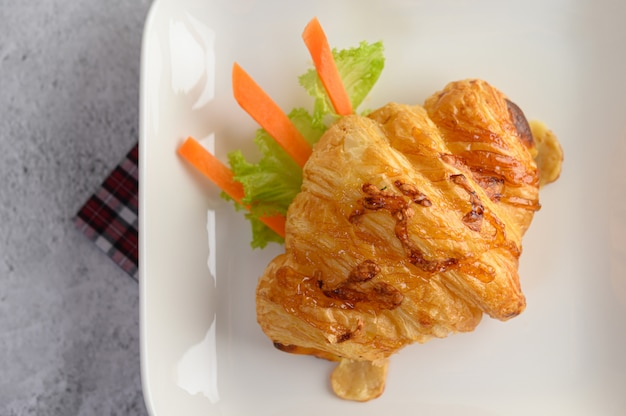 Croissant con hot dog en plato blanco