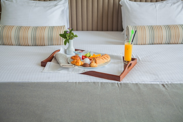 Croissant, huevo cocido, zumo de naranja, desayuno en bandeja en la cama
