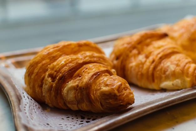 Croissant de mantequilla dulce en una bandeja con papel de encaje. tienda de la ventana de una pastelería. pastelería francesa con hojaldre.