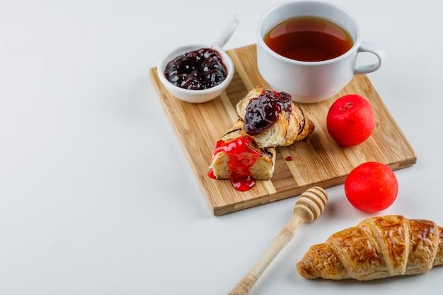 Croissant con mermelada, ciruelas, cazo, vista de ángulo alto de té en blanco y tabla de cortar