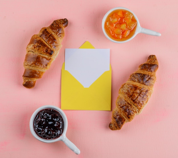 Croissant con mermelada, tarjeta en sobre plano acostado sobre una mesa rosa