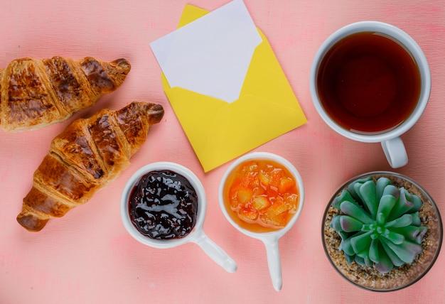 Croissant con mermelada, tarjeta en sobre, planta, té plano sobre una mesa rosa