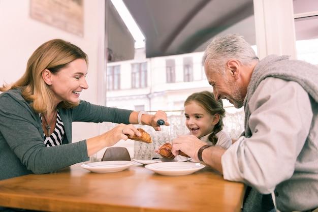 Croissant para niña. abuelos cariñosos y cariñosos dando a su pequeña niña linda croissant fresco