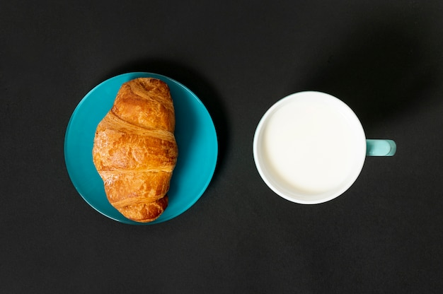 Croissant plano y taza de leche sobre fondo liso