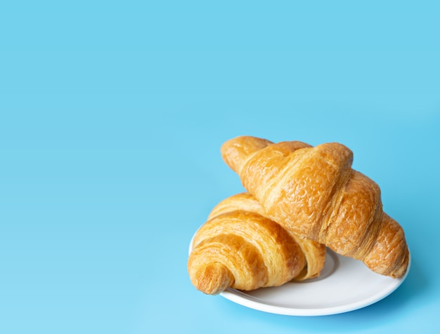 Croissant en un plato blanco sobre fondo de color