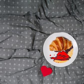 Croissant en un plato cerca del corazón de papel de adorno