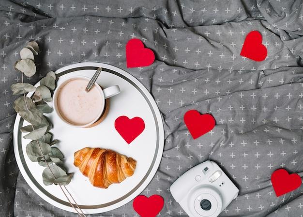 Croissant, ramita y taza de bebida en la bandeja cerca de corazones y adornos de cámara