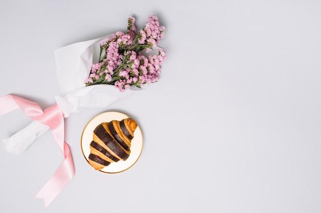 Croissant con ramo de flores en la mesa