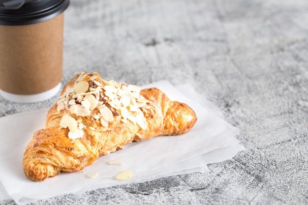 Croissant recién hecho y café en una taza de papel a la luz /