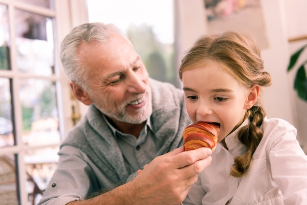 Croissant recién hecho. linda nieta de ojos oscuros mordiendo croissant recién horneado sentado cerca de su abuelo