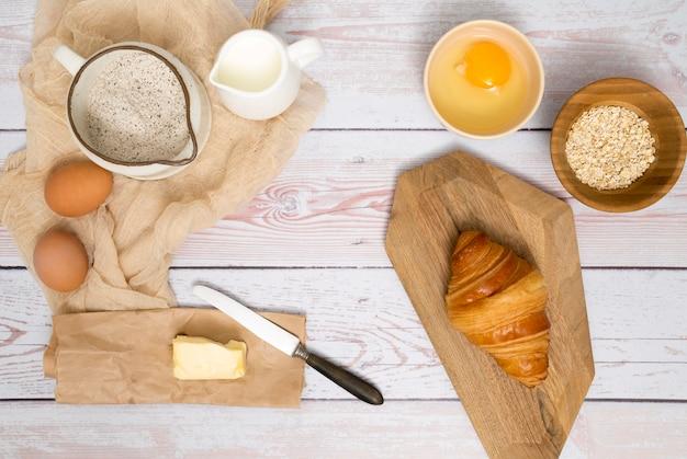 Croissant recién horneado con ingredientes en escritorio de madera