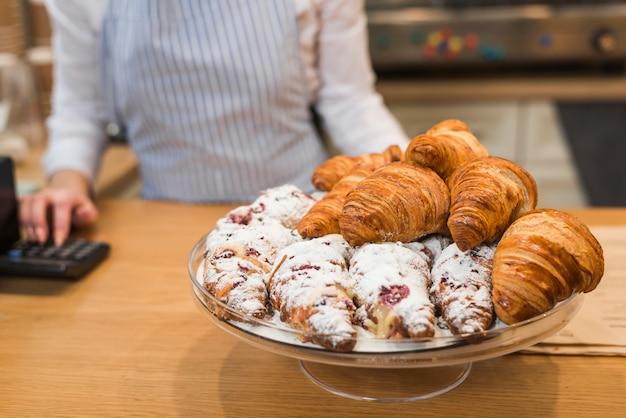 Croissant recién horneado en soporte de pastel en el mostrador de la cafetería