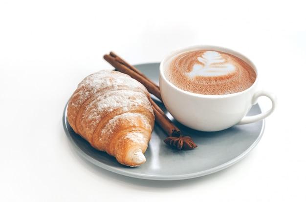 Croissant recién horneado con taza de café y café con leche, canela