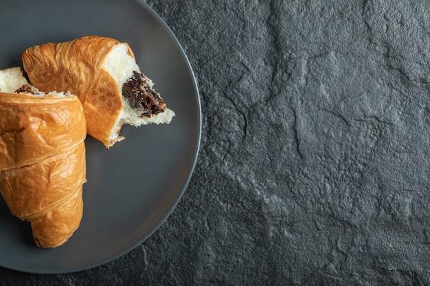 Croissant relleno de chocolate sobre un fondo oscuro.