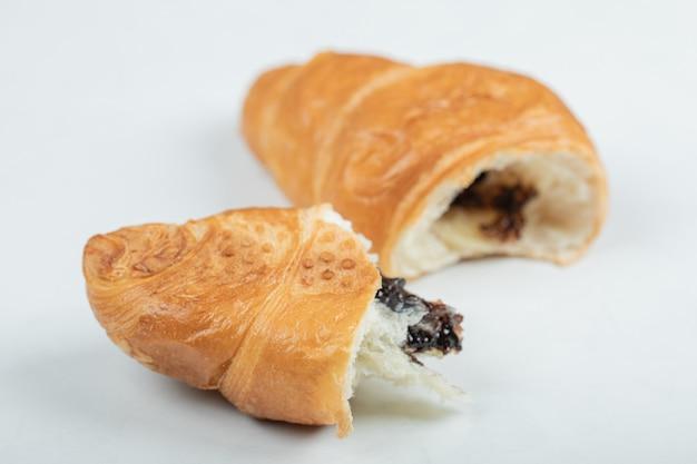 Croissant con relleno de chocolate sobre una superficie blanca.