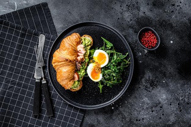 Croissant con salmón ahumado caliente, aguacate, rúcula y huevo. fondo negro. vista superior