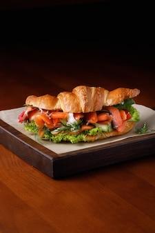 Croissant con salmón y queso crema en la mesa de madera con espacio para copiar texto.