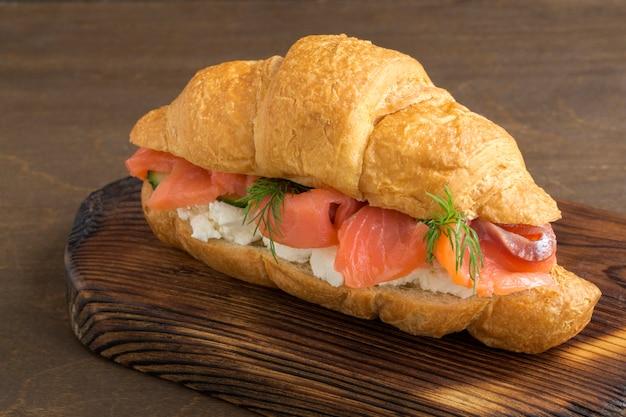 Croissant con salmón y queso crema sobre una plancha de madera.