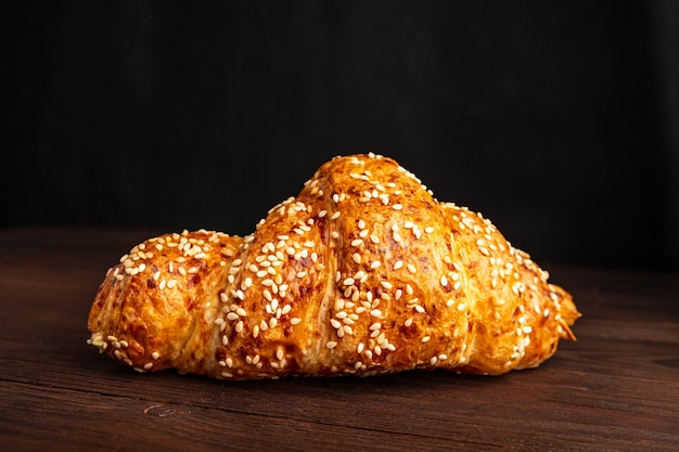 Croissant con semillas de sésamo aislado en una mesa de madera.
